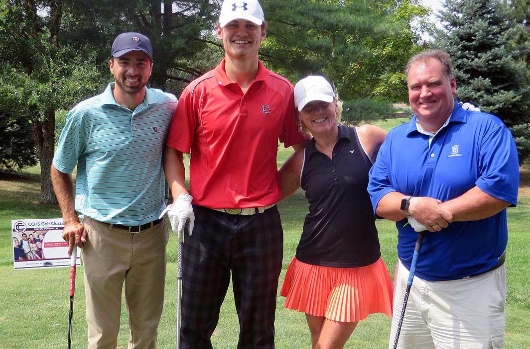 Foursome of golfers standing by the tee, three mena nd one women.