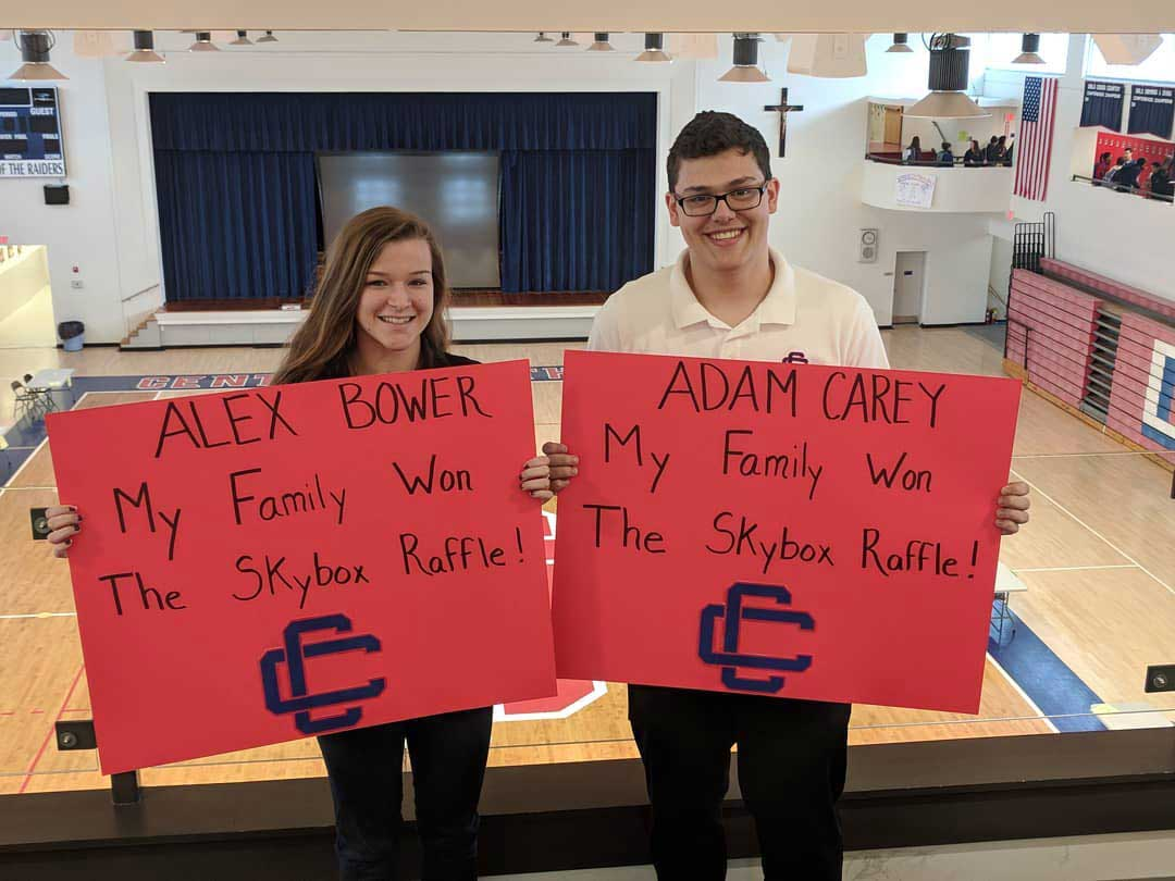 Two students in balcony overlooking the gymnasium holding signs announcing themselves as the winners of the Skybox Raffle.