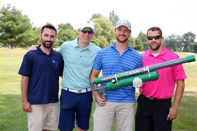 Four golfers, holding a golf cannon to shoot golf balls.