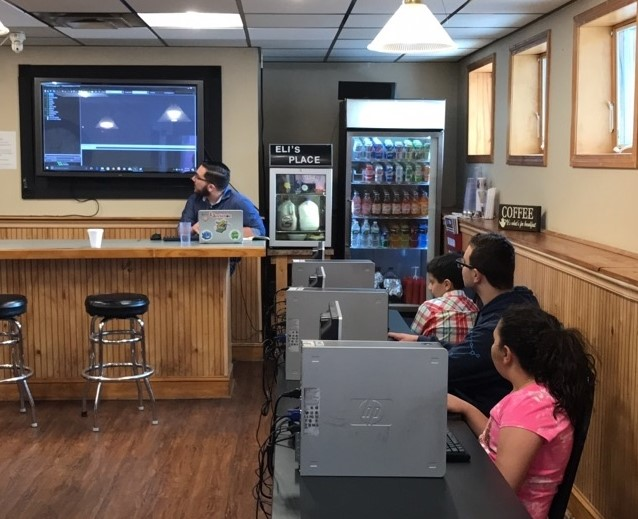 Tyler Haddad '14 teaches some Lawrence children how to code in his parents diner.