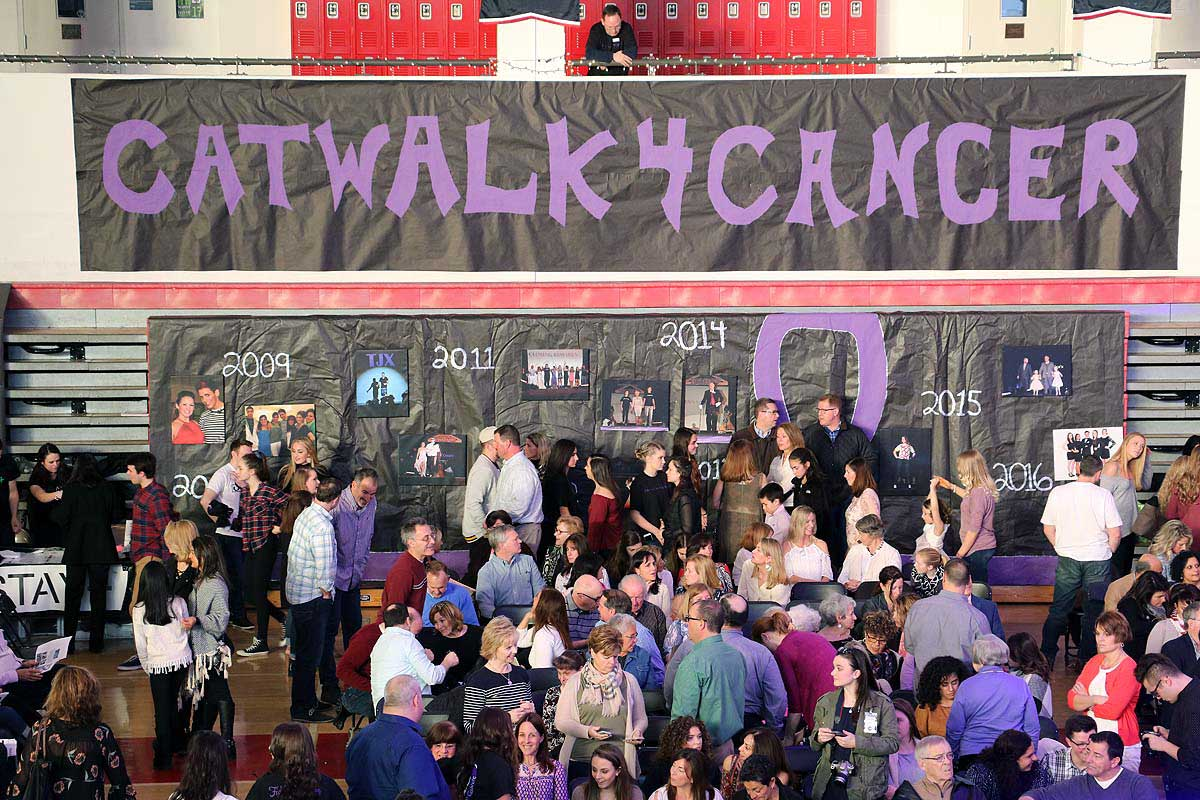 Attendees mingling in gymnasium below Catwalk4Cancer banner,