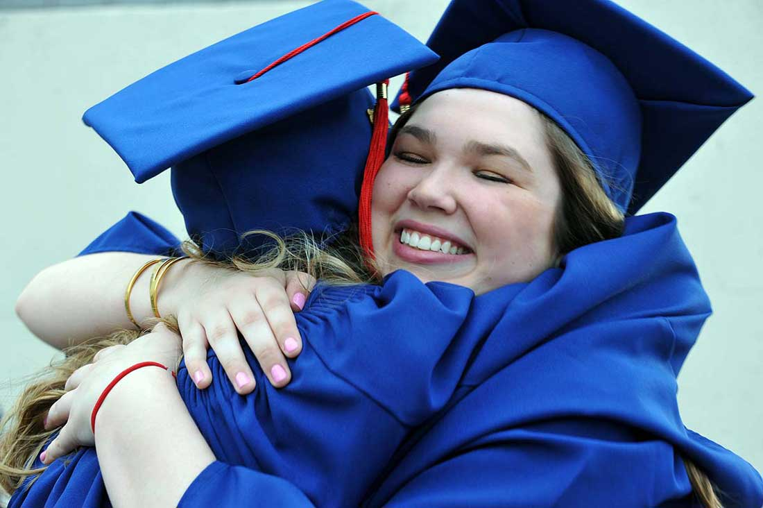 Graduates hug after the 2016 Commencement.