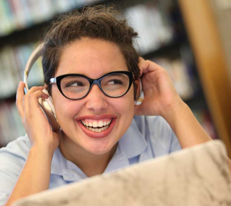 Student listening to headphones in the Library & Media Center.