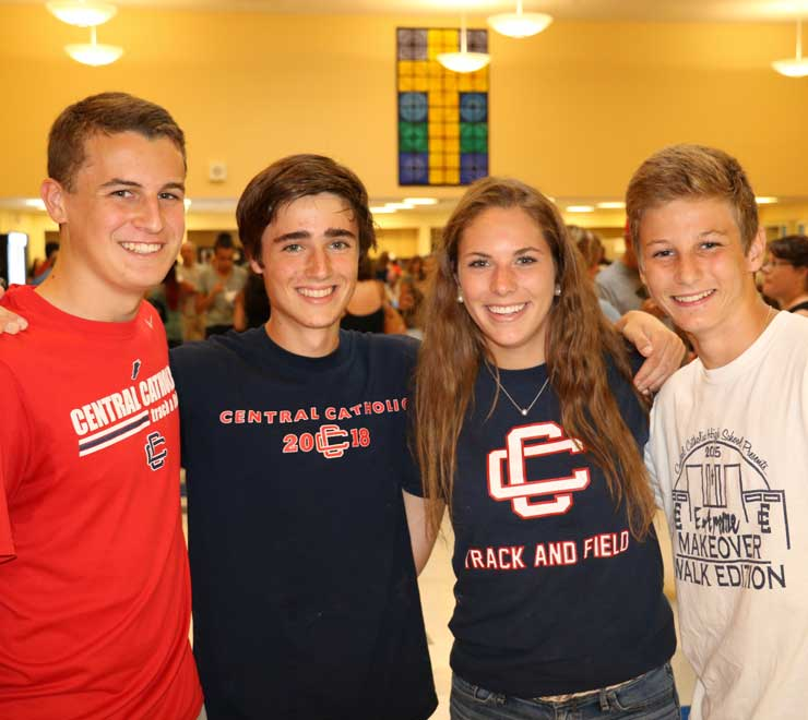 Four smiling students in the Baroni Dining Hall.